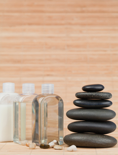 Glass flasks with pebbles and a black stones stackの素材 [FYI00487874]