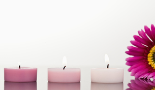 Lighted candles and a pink gerberaの素材 [FYI00487877]