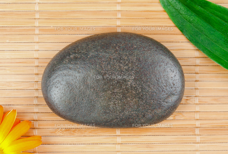 A round smouth pebble surrounded by a leaf and a sunfloverの素材 [FYI00487888]