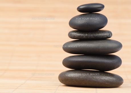 Black stones stack against bamboo backgroundの写真素材 [FYI00487908]