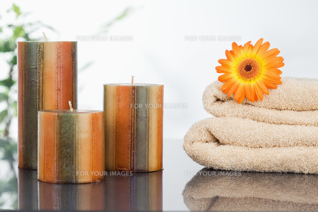 Unlighted candles with an orange gerbera on towelsの素材 [FYI00487916]