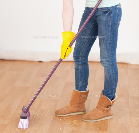 Attractive redhaired woman sweeping the floor at homeの写真素材 [FYI00487919]