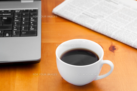 A cup of coffee with a laptop and a newspaperの素材 [FYI00487941]
