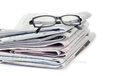 A pair of reading glasses on top of a pile of newspapersの写真素材 [FYI00487955]