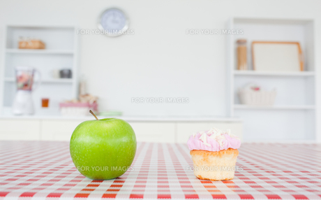 An apple and a cupcake on a tableclothの写真素材 [FYI00488038]