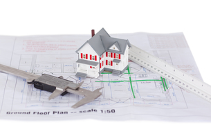 Toy house model and ruler and on a plan against a white backgroundの写真素材 [FYI00488040]