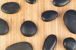 Black stones against bamboo backgroundの写真素材 [FYI00488042]