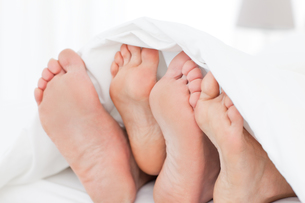 Two members of a family showing their feet while lying on a bedの素材 [FYI00488051]