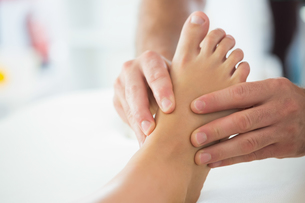 Close up of physiotherapist massaging patients footの写真素材 [FYI00488057]