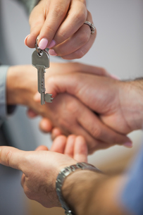 Estate agent giving house key to customer while shaking handsの写真素材 [FYI00488119]