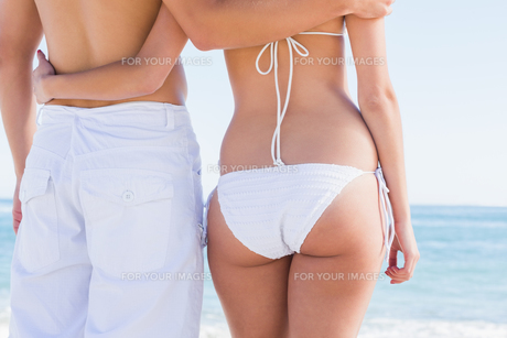 Rear mid section of fit couple facing the seaの写真素材 [FYI00488170]