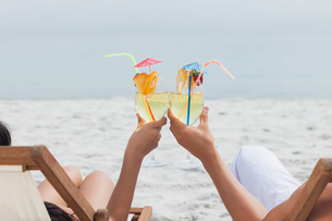 Couple clinking glasses of cocktail on beachの素材 [FYI00488236]