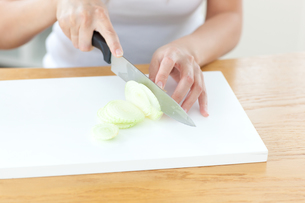 Delighted woman preparing onion in the kitchenの写真素材 [FYI00488273]