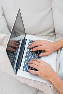 Mans hands typing on laptopの写真素材 [FYI00488275]