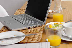 Laptop on a kitchen table. Working having breakfastの写真素材 [FYI00488284]