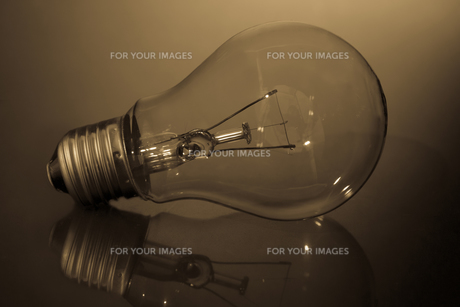 Clear light bulb laying on its side on reflective surfaceの写真素材 [FYI00488320]