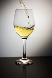 White wine being poured into clear wine glassの写真素材 [FYI00488334]
