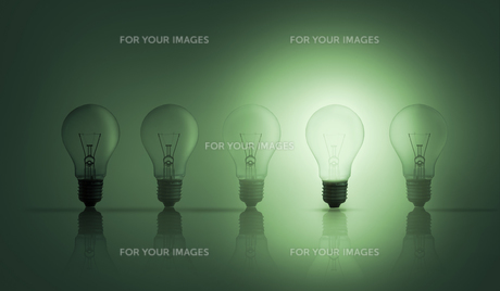 Light bulbs in a row with one lit upの写真素材 [FYI00488336]