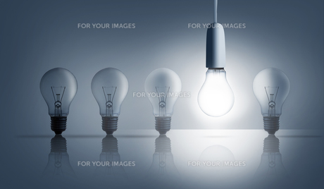 Five light bulbs in a row with one lit upの写真素材 [FYI00488345]
