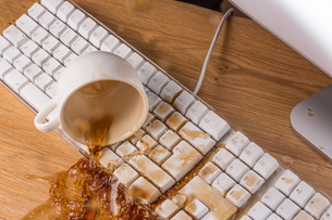 Cup of tea spilling over a keyboardの写真素材 [FYI00488347]