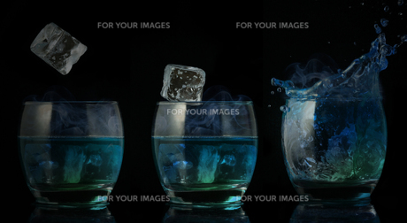 Serial arrangement of ice falling into tumbler of blue liquidの写真素材 [FYI00488356]