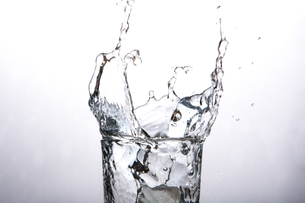 Close up on ice cube falling into glass of waterの素材 [FYI00488379]