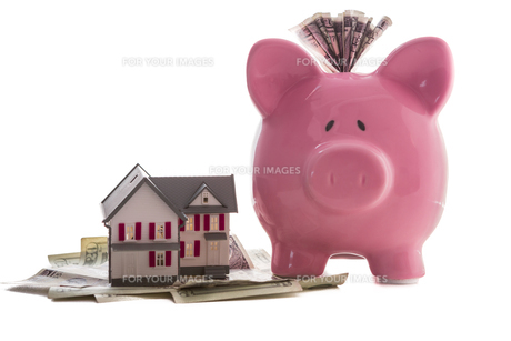 Close up of a pink piggy bank with dollars beside miniature house modelの写真素材 [FYI00488391]