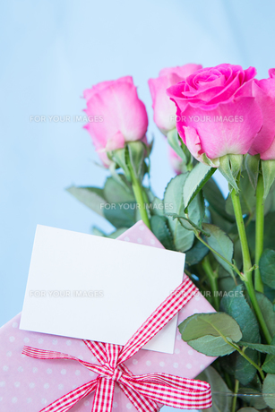 Bouquet of pink roses in vase with pink gift and blank cardの写真素材 [FYI00488433]