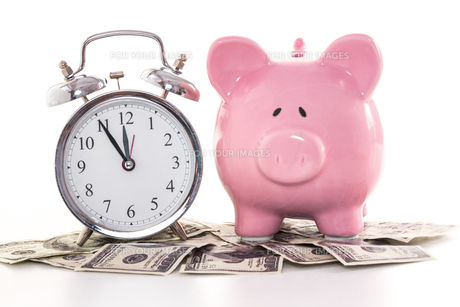 Pink piggy bank beside alarm clock on dollarsの写真素材 [FYI00488437]