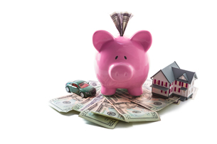 Piggy bank and toy car resting on pile of dollars with mini houseの写真素材 [FYI00488445]