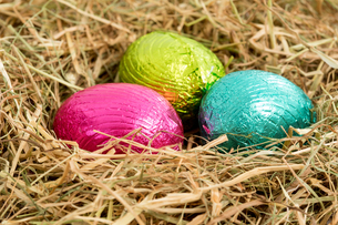 Three colouful easter eggs nestled in straw nestの素材 [FYI00488465]