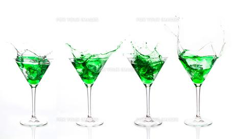 Serial arrangement of green liquid splashing in cocktail glassの写真素材 [FYI00488482]