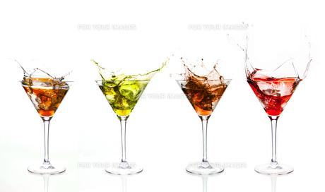Serial arrangement of coloured liquids splashing in cocktail glassの素材 [FYI00488503]