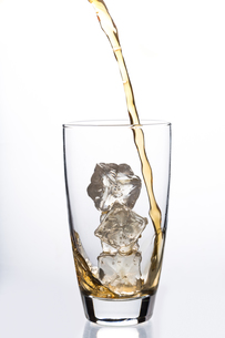 Liquid pouring into glass with ice cubesの写真素材 [FYI00488504]