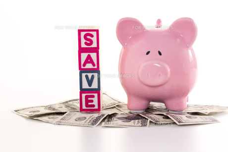 Piggy bank beside save blocks on dollarsの写真素材 [FYI00488505]