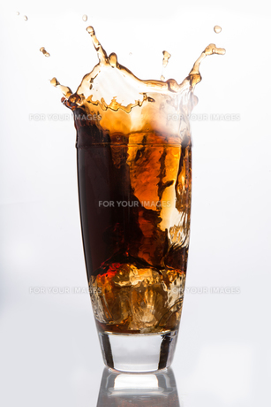Ice cube falling into a glass of sodaの素材 [FYI00488510]