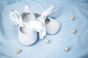 White baby booties on blue blanketの写真素材 [FYI00488544]