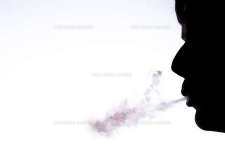 Silhouette of man blowing smokeの素材 [FYI00488567]