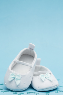 Baby booties with blue ribbon and copy spaceの写真素材 [FYI00488628]