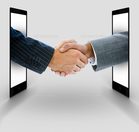 Businessmen shaking hands from digital tabletsの写真素材 [FYI00488657]