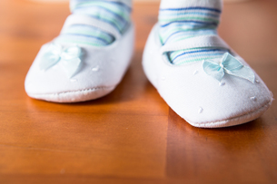 Baby in booties taking first stepの写真素材 [FYI00488658]