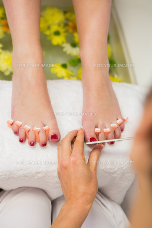 Woman polishing toe nails at spa centerの写真素材 [FYI00488670]