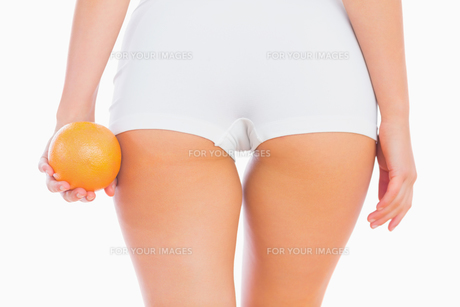 Midsection of woman holding orangeの写真素材 [FYI00488672]