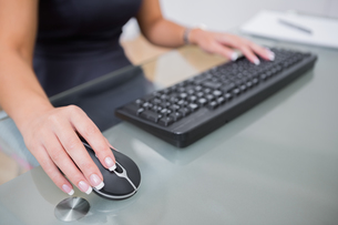 Woman using computer mouse and keyboard at deskの写真素材 [FYI00488675]
