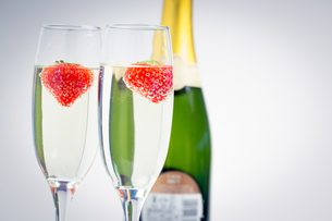 Two champagne flutes with floating strawberriesの素材 [FYI00488679]
