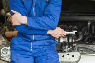 Mechanic leaning on carの写真素材 [FYI00488683]