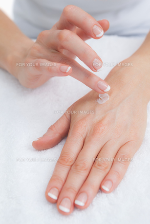 Woman applying cream on handの写真素材 [FYI00488693]