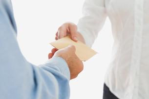 Businessman handing over envelop to coworkerの素材 [FYI00488702]