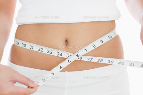 Closeup midsection of woman measuring waistの素材 [FYI00488756]