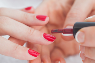 Details shot of hands applying red nail varnish to nailsの素材 [FYI00488762]